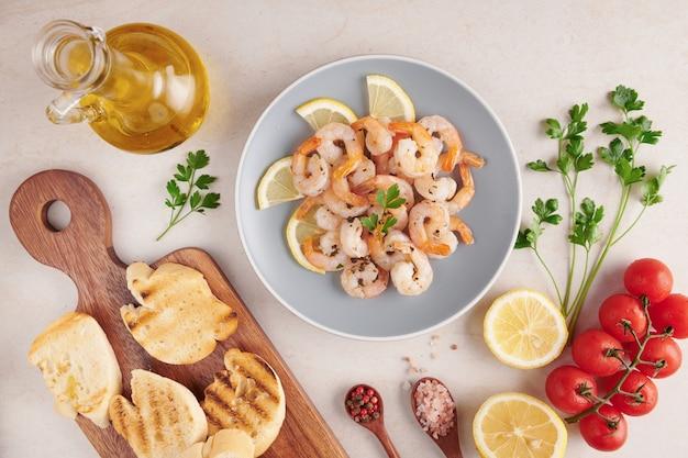 Olive, olio, gamberi alla griglia e insalata di verdure fresche su una tavola di legno su un bordo di pietra ardesia nera su superficie chiara, pomodori succosi su pane fresco, pesto come condimento. vista dall'alto. lay piatto