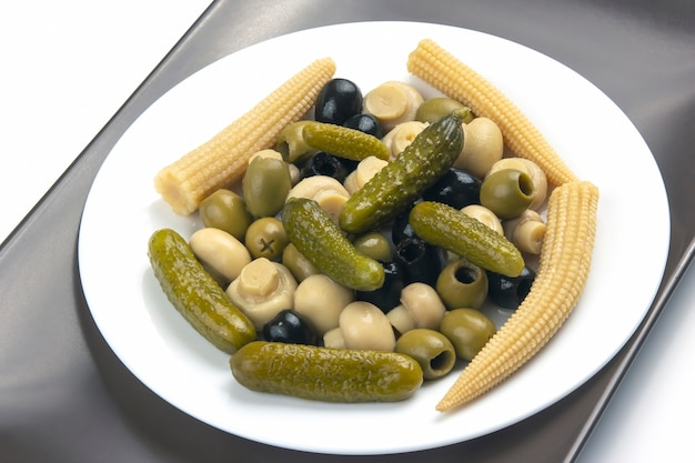 Olives, pickled cucumber, mushrooms and corn in a salad on a plate.