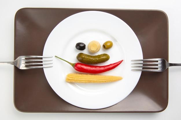 オリーブ、きゅうりのピクルス、コショウ、マッシュルーム、コーンをサラダに盛り付けます。食べ物と野菜。