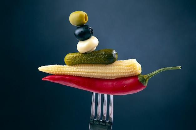 オリーブ、キュウリのピクルス、赤唐辛子、キノコ、トウモロコシのフォークのクローズアップ。食べ物と野菜