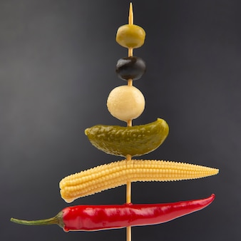 Olives, pickled cucumber, red hot peppers, mushrooms and corn on a wooden stick