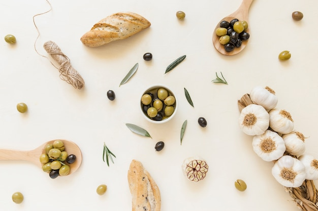 Olives in plate and spoons with garlic and bread