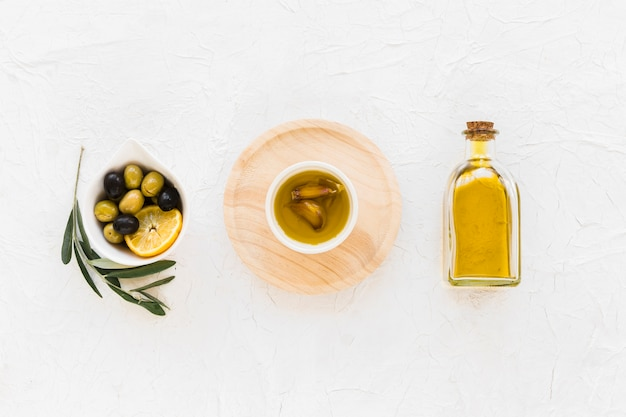 Olives with lemon slice and oil with garlic clove on white background
