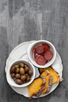 Olives with smoked sausages and corn bread