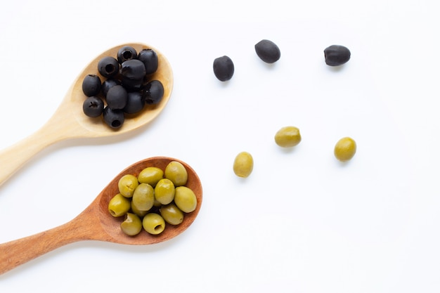 Olives on wooden spoon, white background.