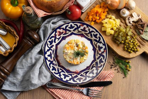 オリビエサラダ-伝統的なウズベキスタンのプレートに野菜、ソーセージ、マヨネーズの伝統的なロシア風サラダ