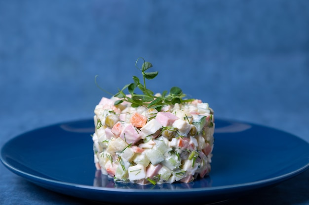 Olivier salad on a blue plate, decorated with pea sprouts. traditional new year and christmas russian salad. close-up, selective focus, blue background.