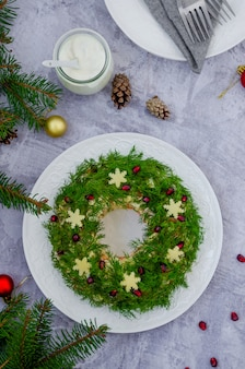 Olivier salad christmas wreath with vegetables, meat (sausage), eggs and mayonnaise on a plate on a gray surface