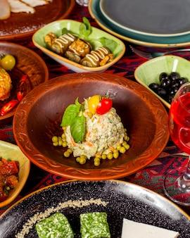 Insalata olivier decorata con piselli, pomodori e basilico