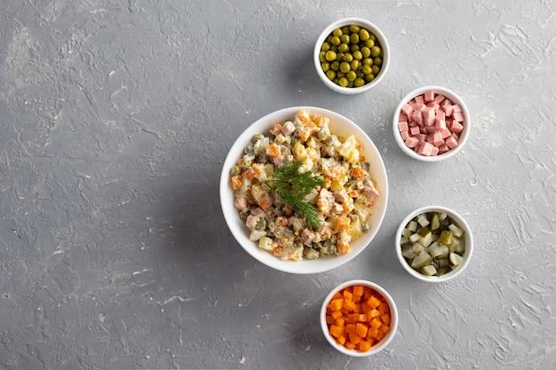 Салат оливье в белой миске и основные ингредиенты зеленый горошек