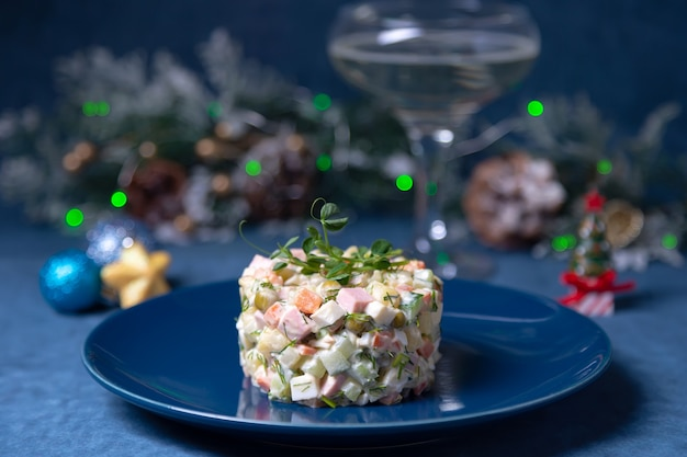 Салат оливье на голубой тарелке, украшенный ростками гороха