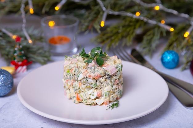 Салат оливье на белой тарелке, украшенной ростками гороха традиционный новогодний и рождественский русский салат крупным планом выборочный фокус