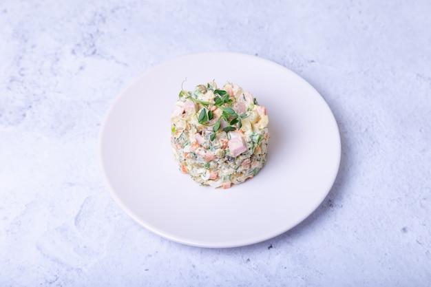 Салат оливье на белой тарелке, украшенный ростками гороха.