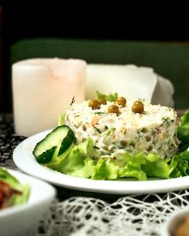 Салат оливье с ломтиками огурца и листьями салата