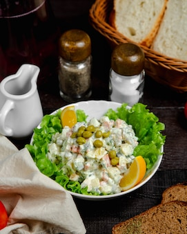 Olivier salad served with lemon