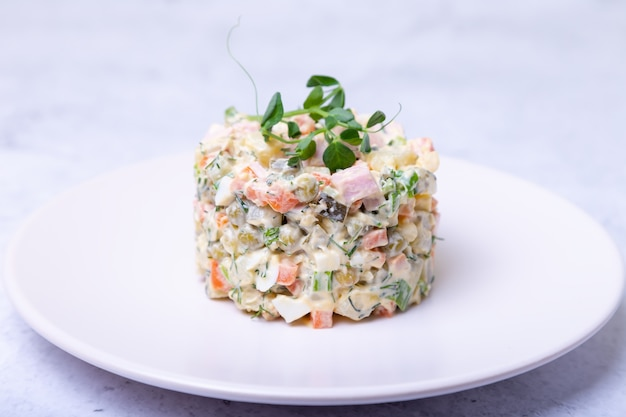 Olivier salad on a white plate, decorated with pea sprouts. russian salad.
