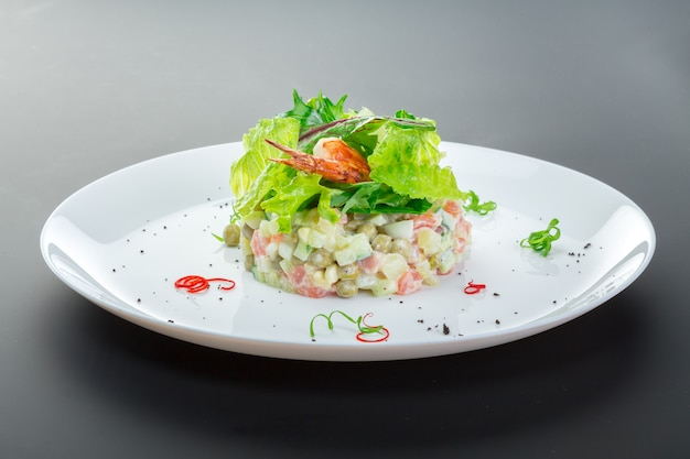 Olivier salad with chicken in a white plate