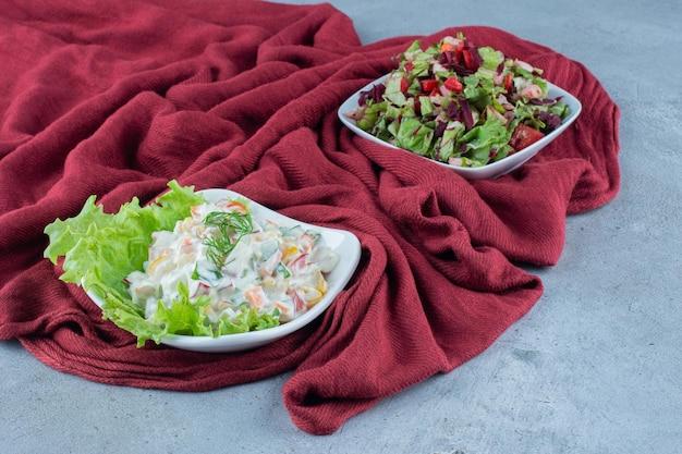 Insalata olivier con lattuga e insalata mista di verdure in ciotole sulla tovaglia sulla superficie in marmo