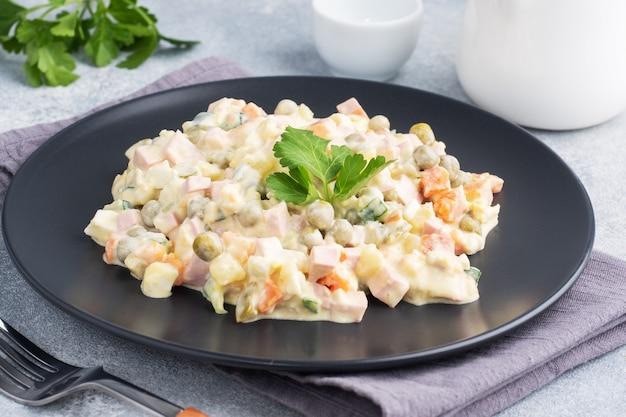 Салат оливье с майонезом на тарелке. русский язык - традиционное праздничное блюдо.