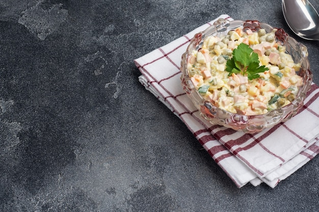 Салат оливье с майонезом на тарелке