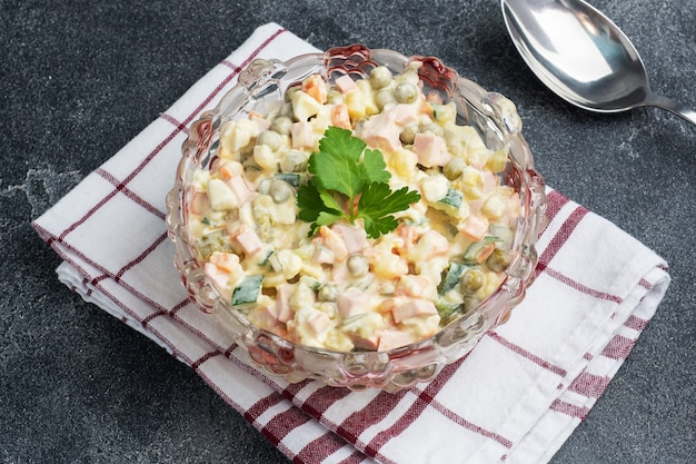 Olivier salad with mayonnaise on a plate. russian is a traditional festive dish.