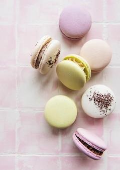 ピンクのタイルの表面に華やかなフランスのマカロン