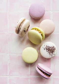 Ð¡olorful french macaroons on pink tile surface