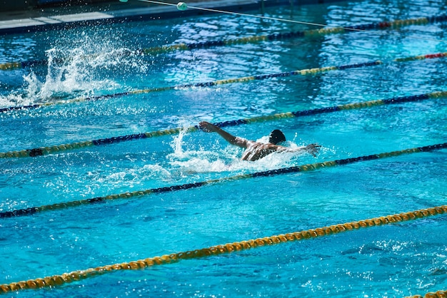 Олимпийский спортивный бассейн с купающимися в воде людьми до неузнаваемости.