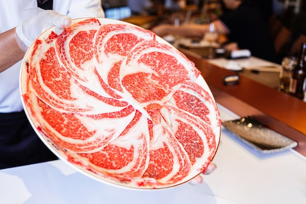 Omakase chef presents premium rare slices of kagoshima wagyu beef with a high-marbled texture on a circle plate