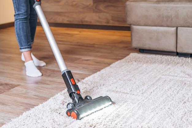 집에서 무선 진공 청소기로 바닥과 카펫을 청소하는 오만.