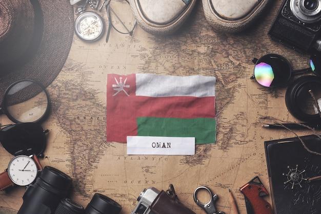 Флаг омана между аксессуарами путешественника на старой винтажной карте. верхний выстрел