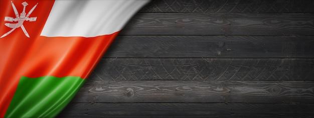 Oman flag on black wood wall. horizontal panoramic banner.