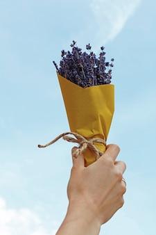 노란 종이에 싸인 말린 라벤더 꽃의 꽃다발을 들고 오만 손