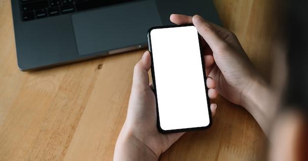 Оман рука смартфон на рабочем месте. мобильный телефон с пустым экраном для монтажа графического дисплея