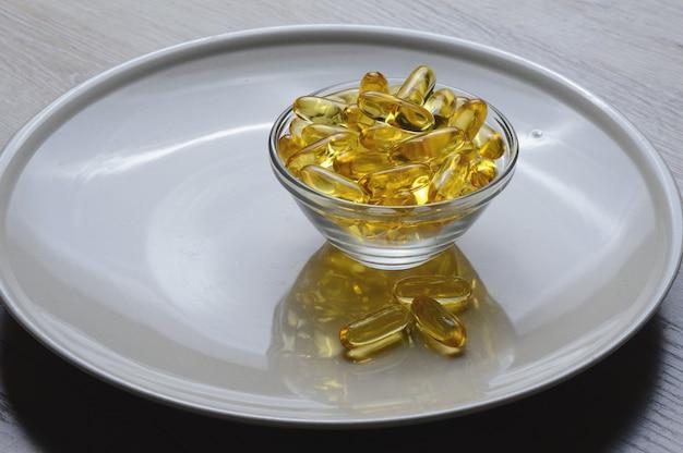 유리 접시에 담긴 오메가 -3 및 비타민 d 어유 캡슐