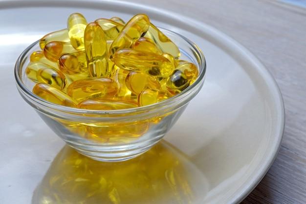ガラス板にオメガ3とビタミンdの魚油カプセル。