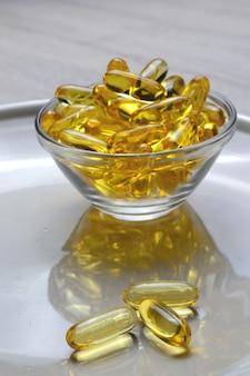 Капсулы рыбьего жира с омега-3 и витамином d в стеклянной тарелке.