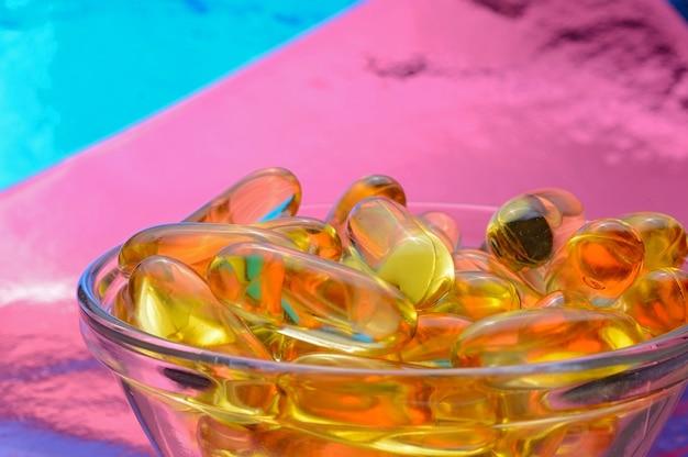 オメガ3カプセル。色付きの背景のガラスのボウル。