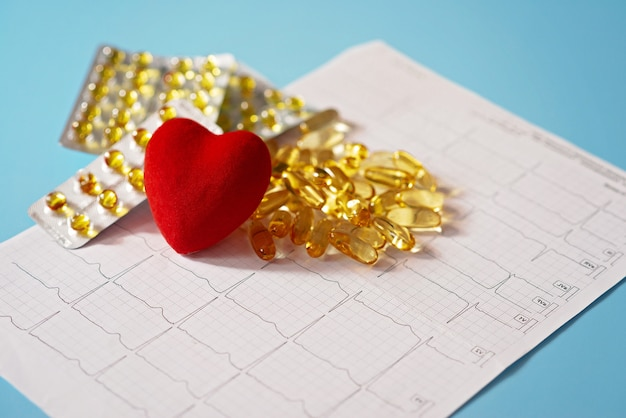 Omega-3 capsules on a cardiogram next to a red heart