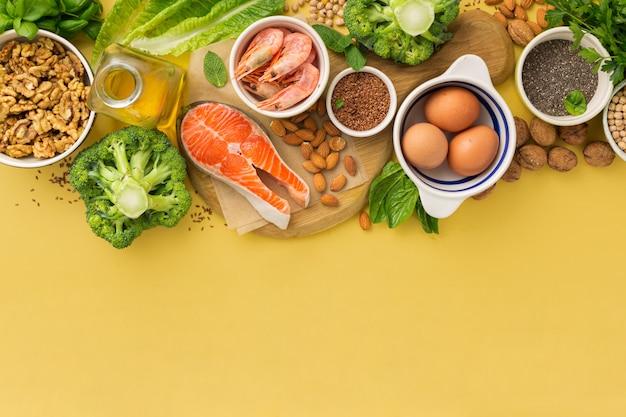 黄色の背景の上面にオメガ3の食料源とオメガ6。野菜、魚介類、ナッツ、種子などの脂肪酸を多く含む食品