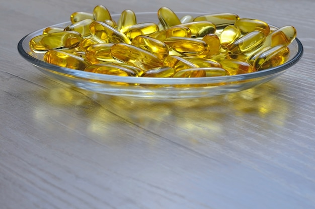 Omega-3 and vitamin d fish oil capsules in a glass plate.