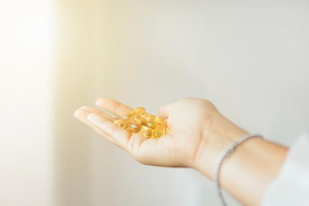 Женская рука держа капсулу дополнения рыбьего жира omega 3