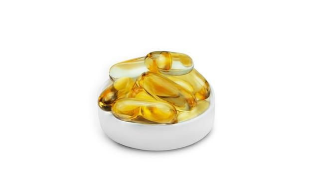 Omega capsules on white background