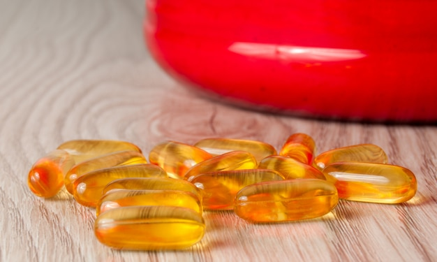 Omega3 fish oil capsules in shape on wooden background