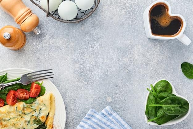 明るい灰色の背景に、白い皿にほうれん草、チェリー トマト、コショウの調味料を入れたオムレツまたはオムレツ。健康的な朝食のコンセプト。上面図。