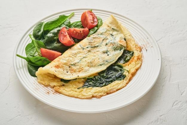 白い背景に、白い皿にほうれん草、チェリー トマト、コショウの調味料を入れたオムレツまたはオムレツ。上面図。