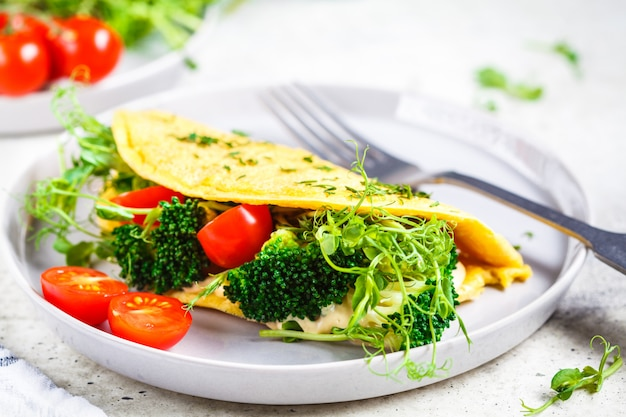 Omelet with broccoli, tomatoes and seedlings. healthy vegan food concept.