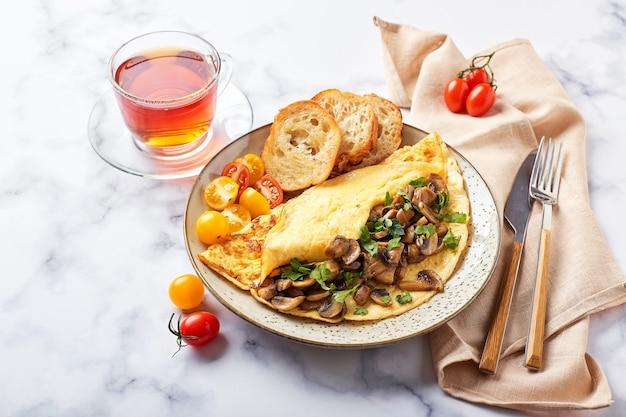 Champignons와 대리석 배경에 접시에 파 슬 리 오믈렛. frittata-아침 또는 점심을위한 이탈리아 오믈렛.