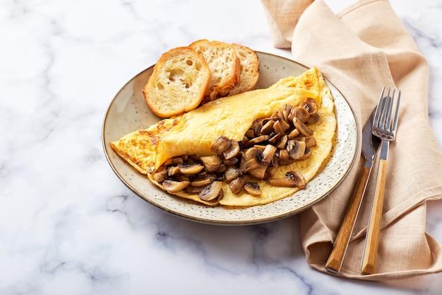大理石の背景のプレートにシャンピニオンとオムレツ。フリッタータ-朝食または昼食用のイタリアンオムレツ。