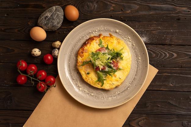치즈, 체리 토마토 및 arugula가 들어간 오믈렛은 어두운 나무 테이블에 아름답게 제공됩니다.